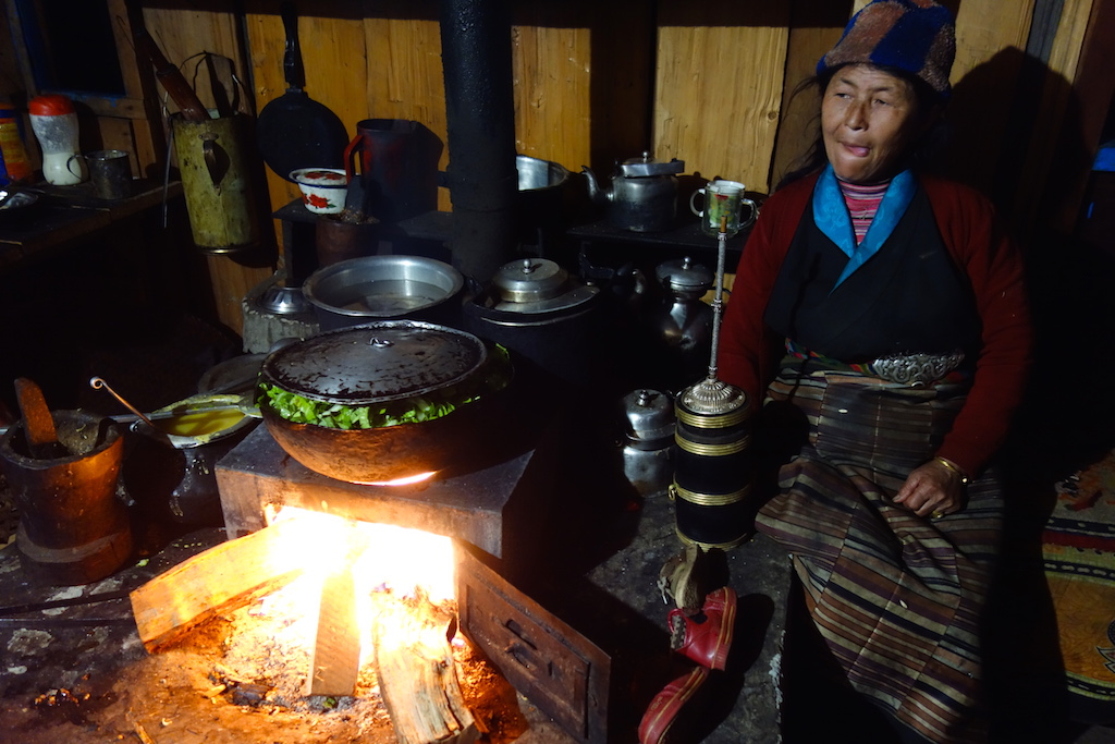 Tibetan woman in the kitchen drinking Tongba.